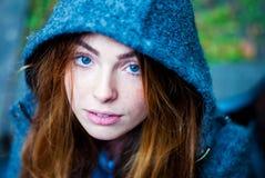 Lugna flicka med blåa ögon i huven Arkivbild