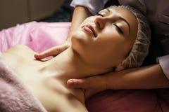 Lugna flicka som har ansikts- massage för brunnsort i lyxig skönhetsalong arkivfoto