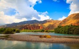 Lugna flod bland de röda bergen Arkivbild