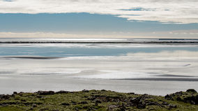 Lugna glödande morgonljus över en isländsk fjord Fotografering för Bildbyråer