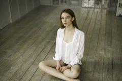Lugna härlig ung kvinna i en vit klänning hemma Arkivbild