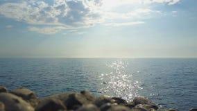 Lugna hav, en varm solig dag Solen är på horisonten Det finns stenar framme lager videofilmer