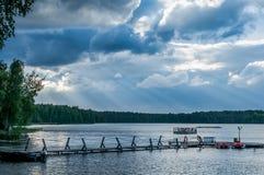 Lugna himla- landskap med tjocka moln över skogsjön, tyst ställe som ska kopplas av Fotografering för Bildbyråer