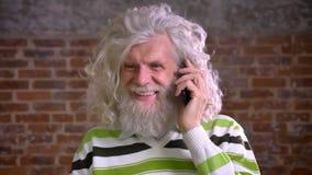 Lugna konversation över telefonen av den gamla caucasian mannen med det stora vita skägget och krabbt hår, fokuserade nolla hans  lager videofilmer