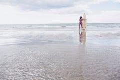 Lugna kvinna i bikini med surfingbrädan på stranden Royaltyfri Fotografi