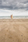 Lugna kvinna i bikini med surfingbrädan på stranden Royaltyfri Bild