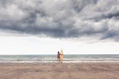Lugna kvinna i bikini med surfingbrädan på stranden Arkivfoton