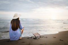Lugna kvinna som bara sitter p? en sandaftonstrand arkivfoto