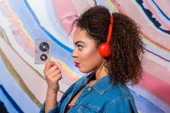 Lugna kvinna som håller ljudbandet i arm Arkivbild