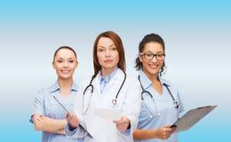 Lugna kvinnlig doktor med skrivplattan Arkivbild