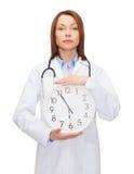 Lugna kvinnlig doktor med väggklockan Royaltyfri Fotografi