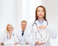 Lugna kvinnlig doktor med väggklockan Royaltyfria Bilder