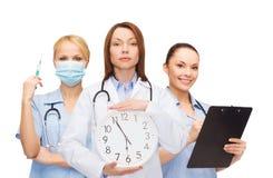 Lugna kvinnlig doktor och sjuksköterskor med väggklockan Arkivbilder