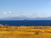 lugna lake för blue Blåa berg som täckas av moln Guld- gräsFied kust arkivbild