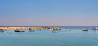 Lugna medelhav med klar himmel, små fartyg och den lilla ön på kusten av Alexandria, Egypten Arkivfoto