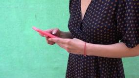 Lugna moderiktig flicka för innehåll i den tillfälliga klänningen som spelar leken i telefonen som isoleras över grön bakgrund arkivfilmer