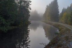Lugna och dimmig morgon nära en kanal i Sverige royaltyfria foton