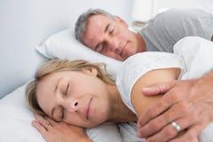 Lugna par som sover och skedar i säng Arkivbild