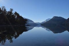 Lugna sjö reflekterade berg fotografering för bildbyråer