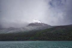 Lugna sjöyttersida med bergmaximumet i bakgrund royaltyfria bilder