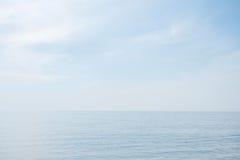 Lugna stillsamt blått hav med inga vågor och med dimmig backgroudn royaltyfri fotografi