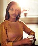 Lugna svart kvinnasammanträde på tabellen med den ljusa solen arkivbild