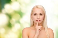 Lugna ung kvinna med fingret på kanter royaltyfri bild