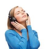 Lugna ung kvinna med hörlurar royaltyfri fotografi