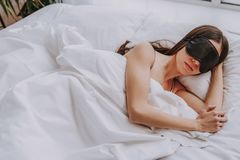 Lugna ung kvinna som sover i ljus säng royaltyfri bild