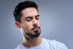 Lugna ung man som mediterar, medan öva yoga hemma Arkivfoto