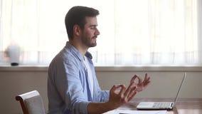 Lugna uppmärksam ung man som tar avbrottet för att sitta på att meditera för skrivbord stock video