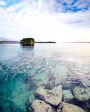 Lugna vatten med stenar och solnedgång fördunklar över havet med ön Royaltyfri Foto