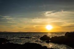 Lugna vatten under solnedgång bak ön arkivbild