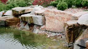 Lugna vattenflöde av den propra konstgjorda vattenfallet med dammet och växter och blommor lager videofilmer