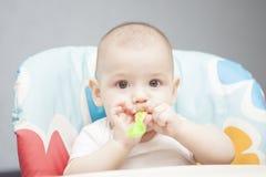 Lugnat caucasian spädbarn i stol med den små skeden Arkivfoto
