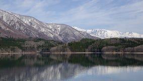 Lugnt vatten, sjön Aoki och snö täckte moutain, Nagano, Japan Royaltyfri Foto