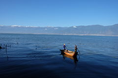 Single boat on Erthai lake. In China, Yunnan province, Pure blue and vast water lake.  Boundless mountains. One yellow boat with two men Royalty Free Stock Photo