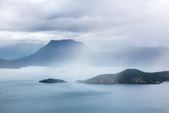 Lugu Lake in service than the rain goddess Gorm Island and distant mountains Royalty Free Stock Photo