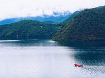 Lugu Lake. Yunnan, China. Summer travel.Red boat with tourists doing a day-long trip around the big lake Stock Photo