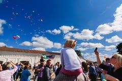 LUH, RUSIA - 27 DE AGOSTO DE 2016: Festival de cebollas en el pueblo de Luh, Rusia Muchacha que mira los globos que vuelan adentr Imagenes de archivo