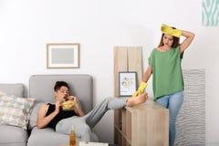 Luie echtgenoot die bij bank en zijn vrouw het schoonmaken liggen stock foto's