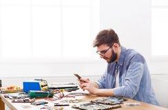 Luie hersteller het spelen smartphone in werkplaats royalty-vrije stock fotografie