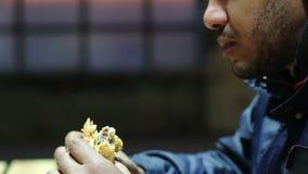 Luie jonge mens die vettige sandwich, ongezonde kostverslaafde kauwen die bovenmatig gewicht bereiken stock videobeelden