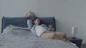 Luie mens die op bed liggen die terwijl de vrouw bezig is dromen stock video
