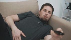 Luie mens die op TV thuis letten stock footage
