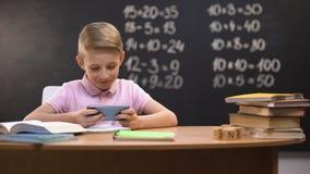 Luie schooljongen het spelen videospelletjes op telefoon in plaats van het voorbereiden van taak, gadget stock footage