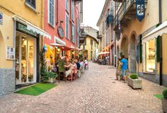 People enjoying the typical italian street bars and restaurants in summer afternoon in the historic center of Luino, Italy. Luino, Lombardy, Italy - July 18 Royalty Free Stock Photo