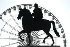 Luis XIV, place Bellecour, Lyon France. The statue of Luis XIV mounted on a horse, place Bellecour, Lyon, France. Silhouette against a carousel ferries wheel Stock Photography