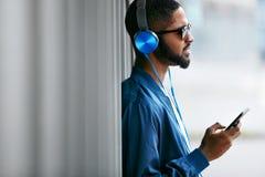 Luister muziek Mens met Hoofdtelefoons en Telefoon in Manierkleren royalty-vrije stock fotografie
