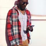 Luistert de jonge Afrikaanse mens van het manierportret aan muziek op smartphone, hipster dragend een plaid rood overhemd en zonn Royalty-vrije Stock Fotografie